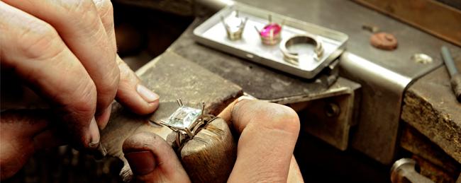 Foto von einem Werkstatt Shooting des Juweliers Rüschenbeck, bei dem ein Stein gefasst wird.